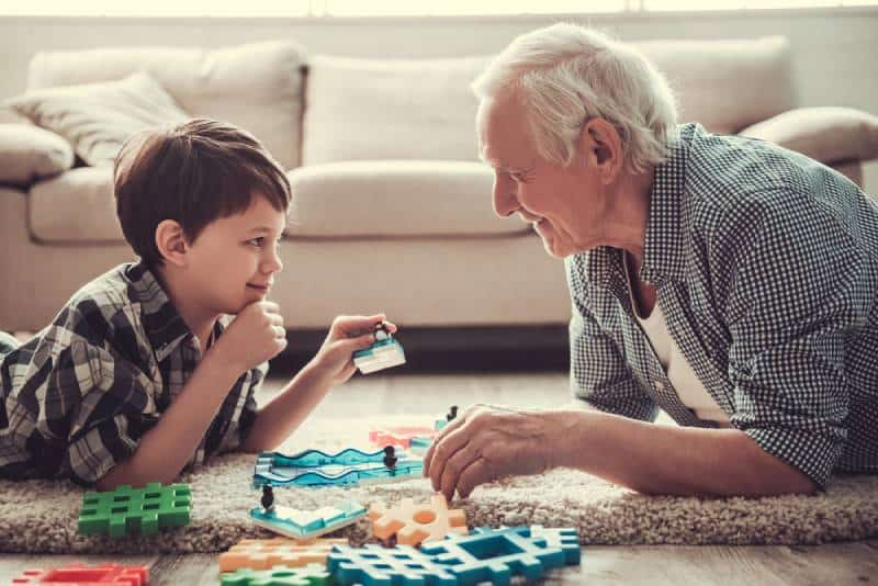 Grandpa and grandson are playing with toys indoors