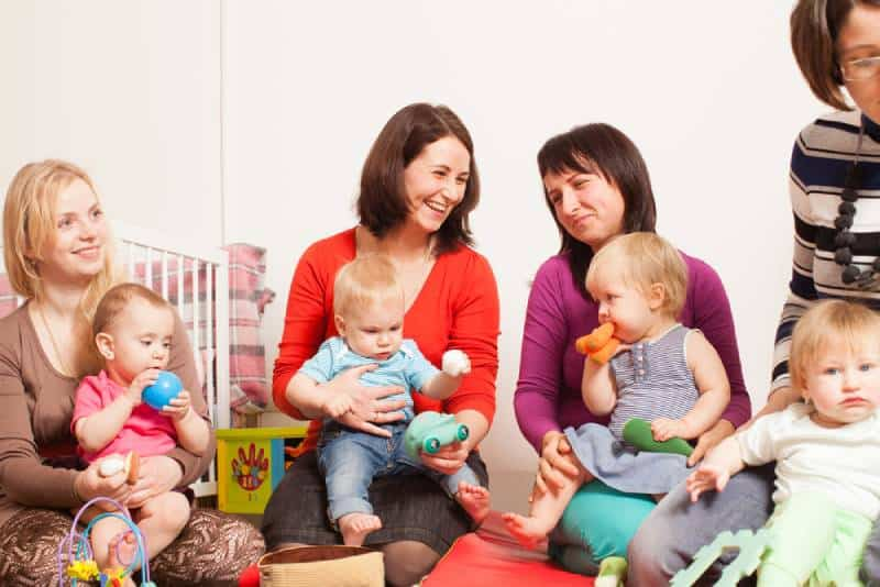 Group of mothers with their babies talking and laughing