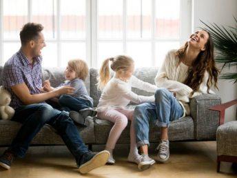Happy parents and kids having fun on sofa