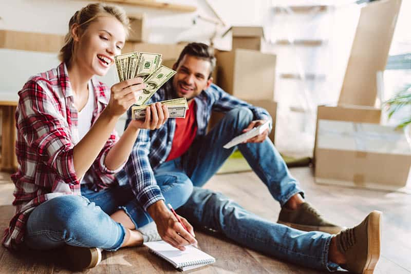 Couple sitting on the floor at home and looking happy for money they saved