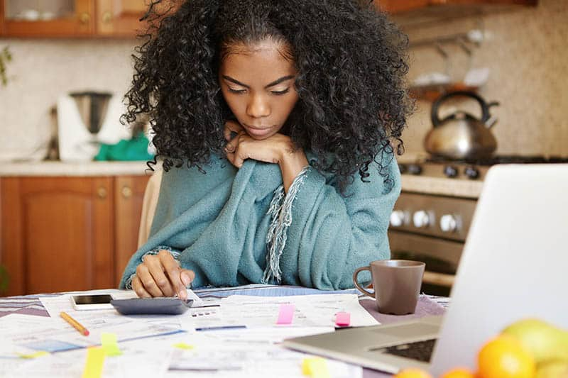 Woman in her kitchen covered with blue blanket doing her finances