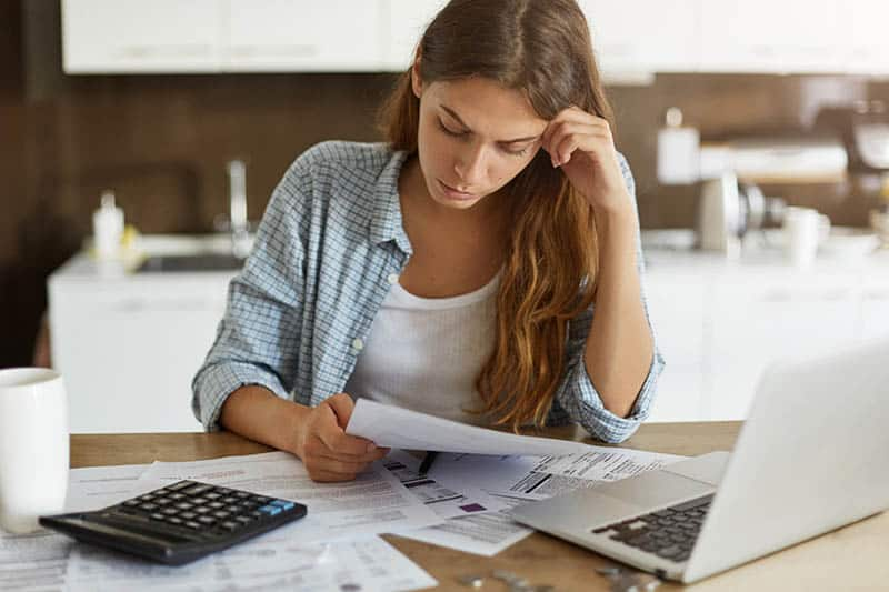 Woman sitting at the table and organizing her bills at home