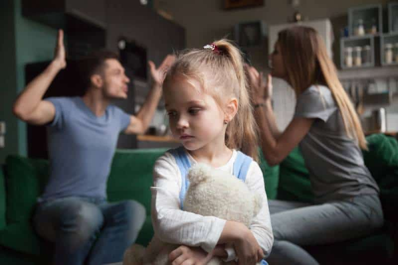 Sad little girl while parents are fighting in the background