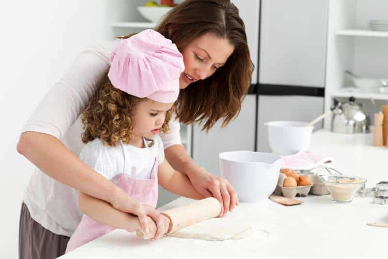 Mother and daughter using a rolling pin in the kitchen