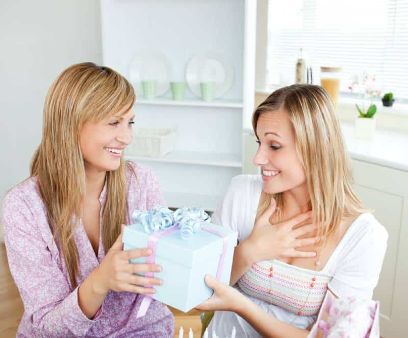 Sister giving a gift for sibling day