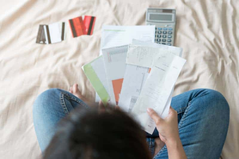 Woman sitting on bed and holding credit card bills