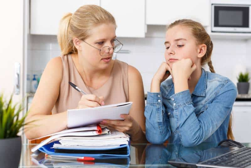 Woman supervising study of her daughter