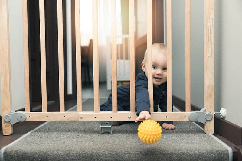 baby boy playing with ball behind baby gate