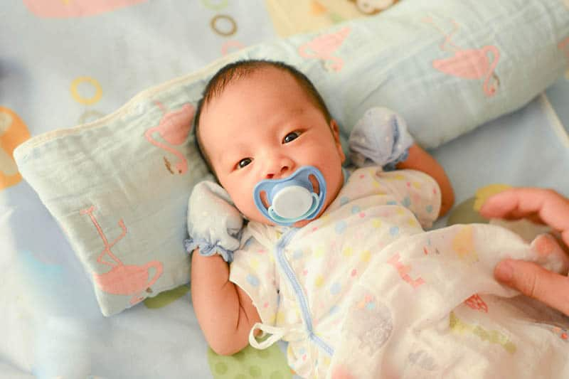 cute asian baby with pacifier lying in bed
