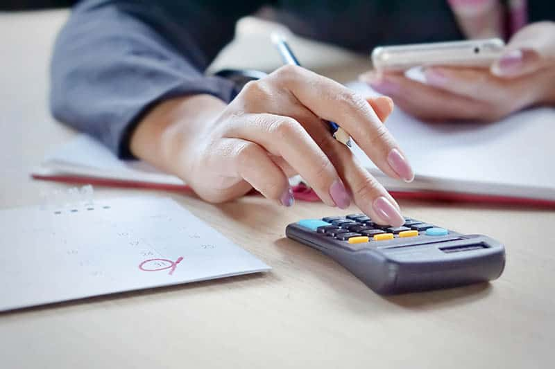 woman calculating her budget with a calculator