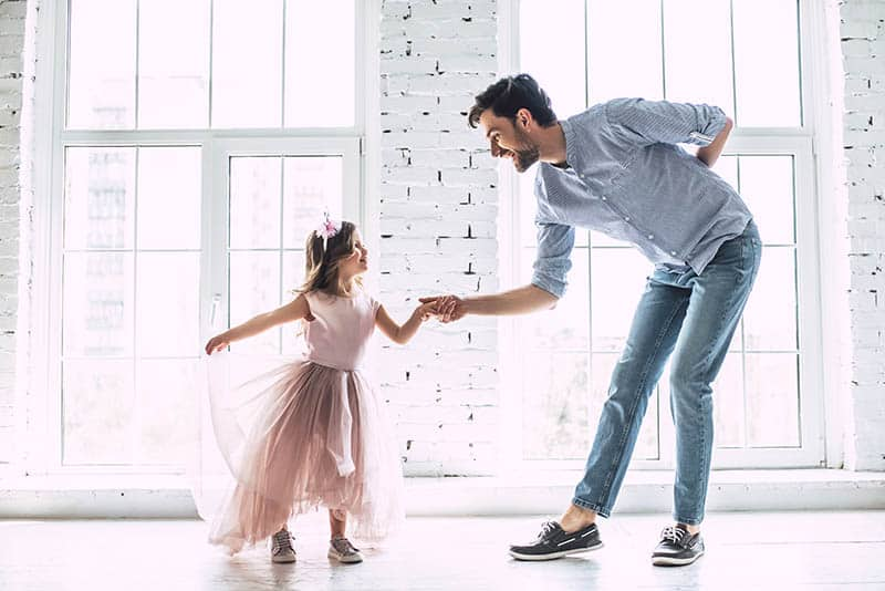 father and daughter are dancing in living room