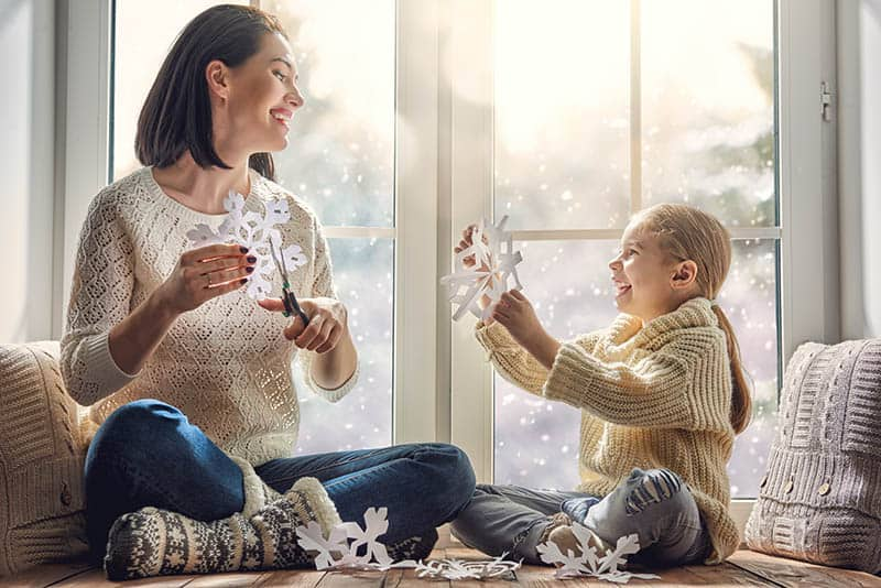 happy mom and girl making Christmas decorations