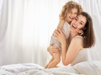 happy mother holding her child on a bed