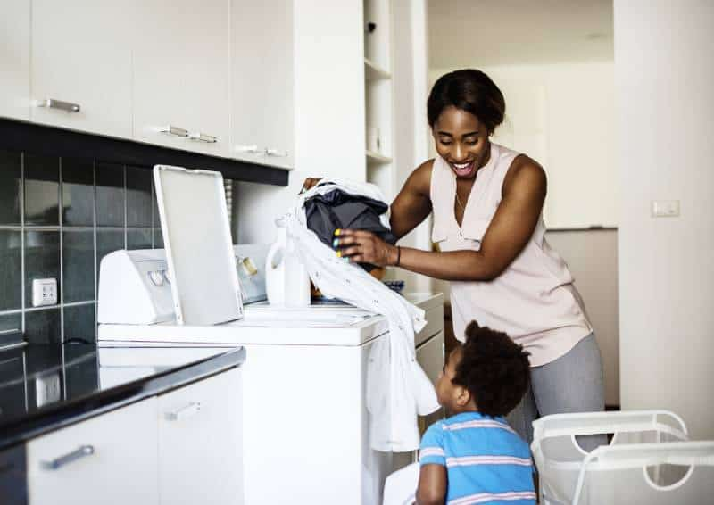 little kid helping mom doing the laundry