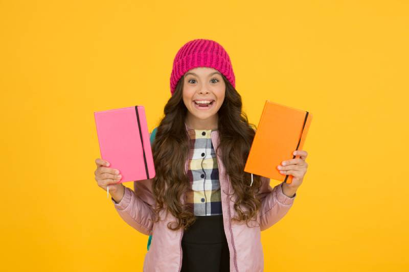 little girl holding textbooks and smiling