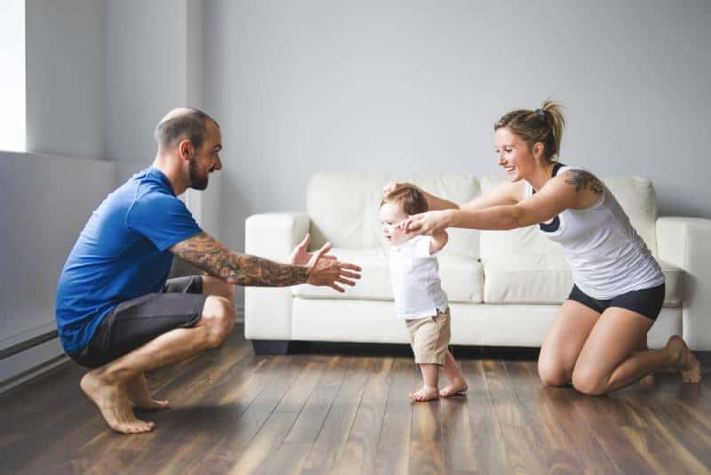 Cheerful mom and dad help their son to walk
