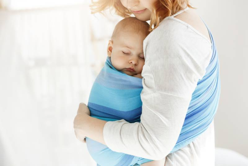 mother holding sleeping baby in baby sling