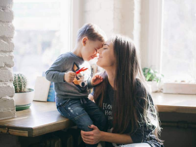 Happy mother kissing her little son