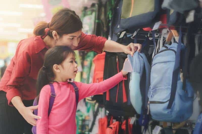 parent and little girl kid buying backpack at the store