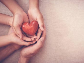 parents holds young kid's hands supporting red heart