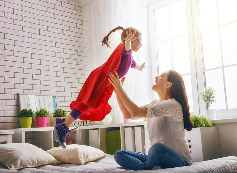 happy mom and girl playing superhero