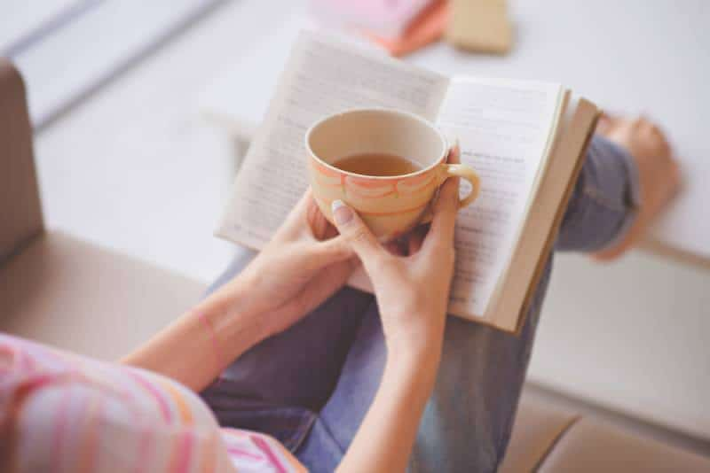 woman holding teacup in front of opened book and enjoying