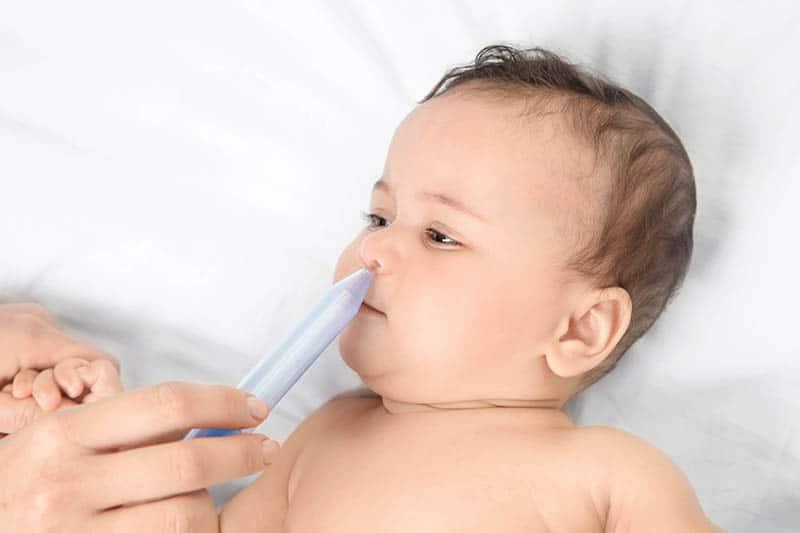 mother giving nasal aspirator to baby