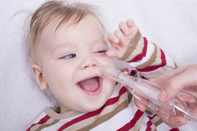 baby laughing while getting a nasal aspirator