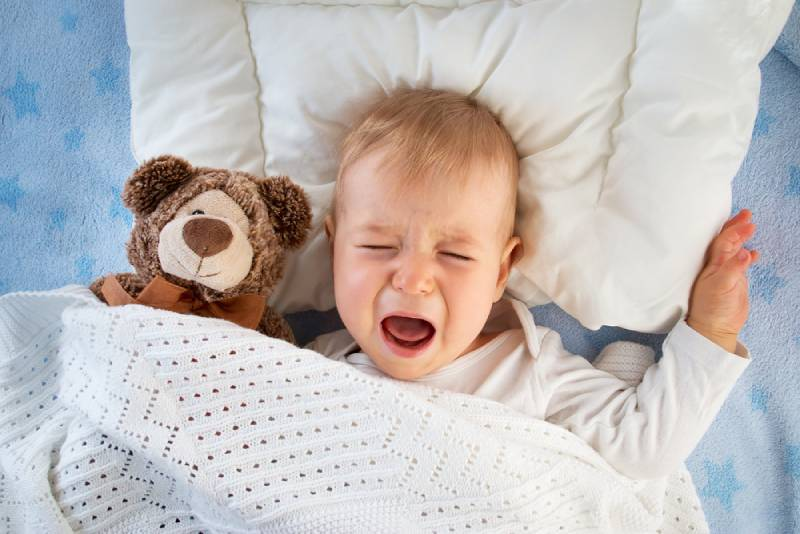 boy crying in bed with a teddy bear
