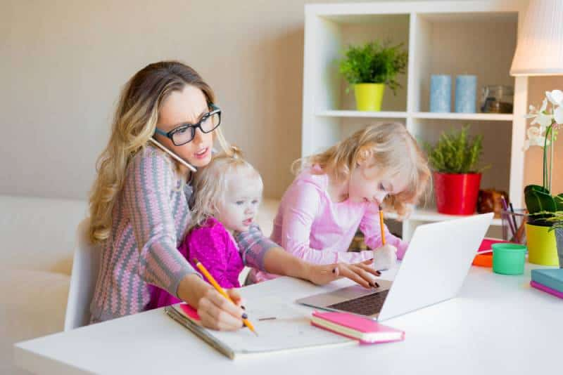 Busy woman trying to work with kids