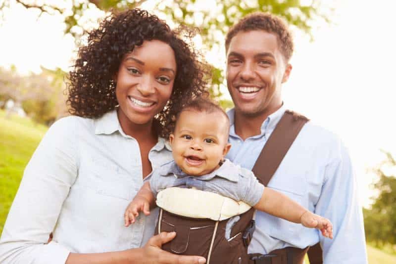 Family With Baby Son In Carrier Walking