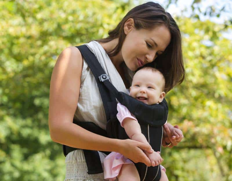 Happy mom with a baby in a carrier enjoying outdoors
