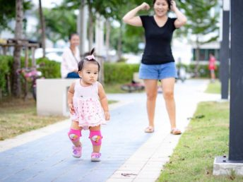 Little baby girl in pink dress and knee pads walking in pavement in park