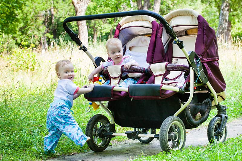 twin babies in lightweight double strollers