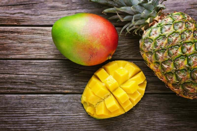 Mango with pineapple on wooden table