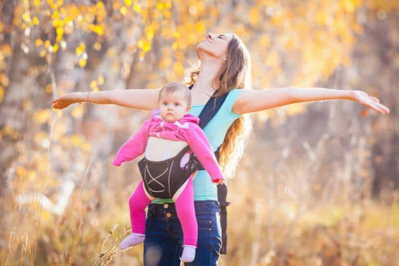 Happy mother carrying her child by ergonomic baby carrier