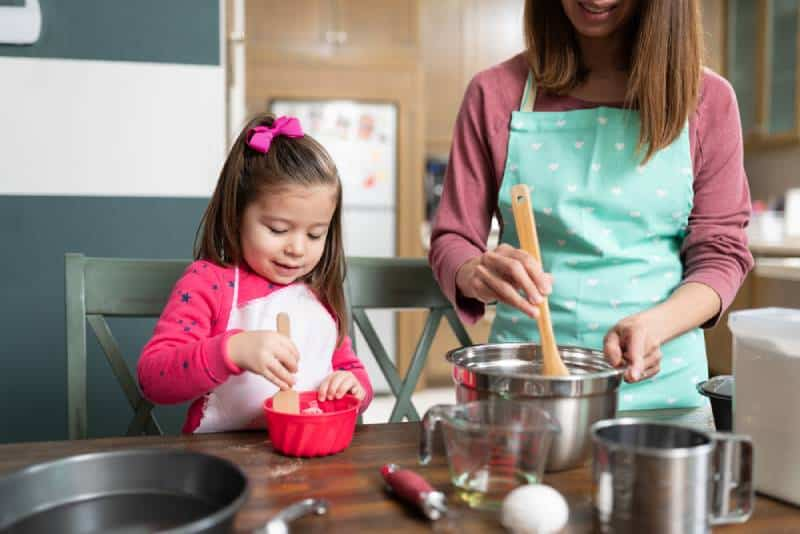 Mom and daughter cooking in kitchen and having fun