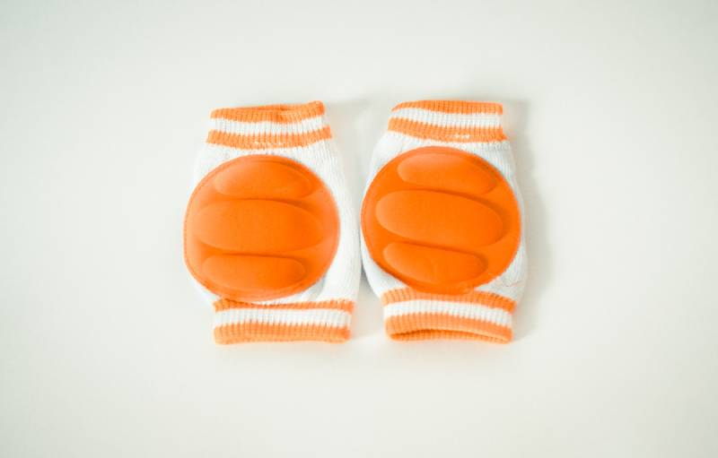 Orange knee pads for babies on light surface