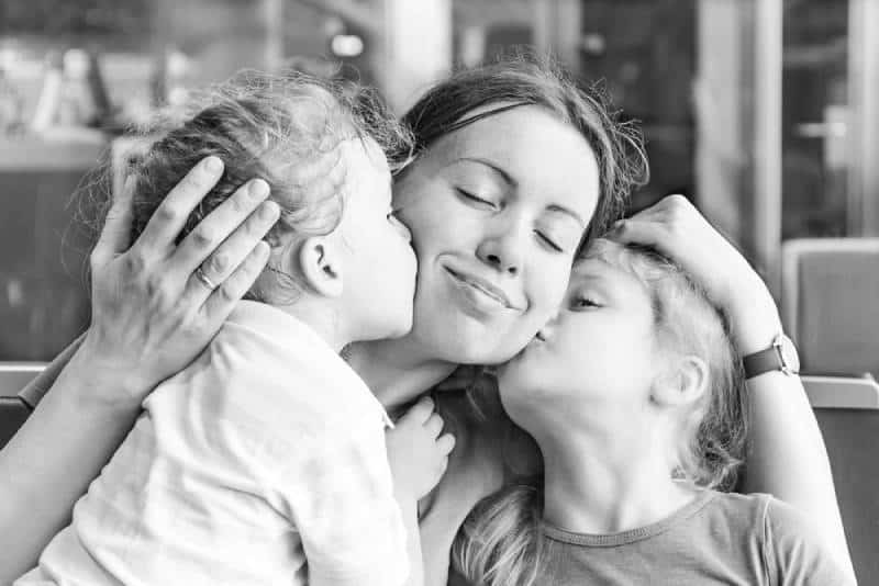 Two daughters kissing their happy mother indoors