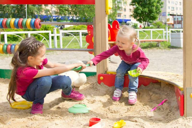 Two kids fighting over a toy shovel in the sandbox