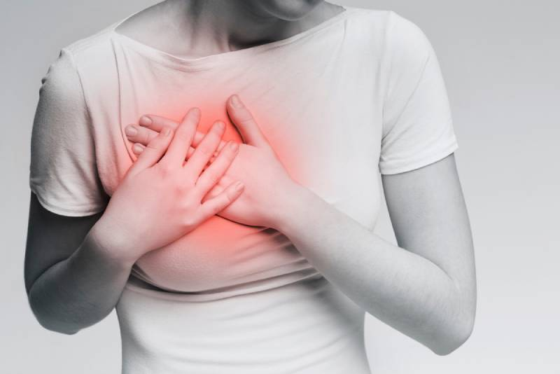woman with breast pain, touching red sore zone on her chest