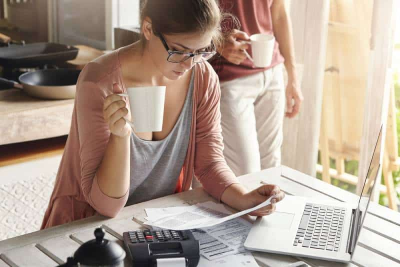 Woman taking care of the finances at her home while drinking a coffee