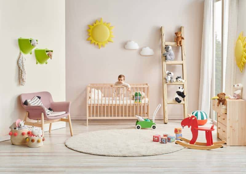 Baby in modern baby room standing in cot bed