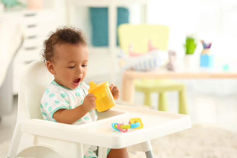 baby playing and eating in high chair