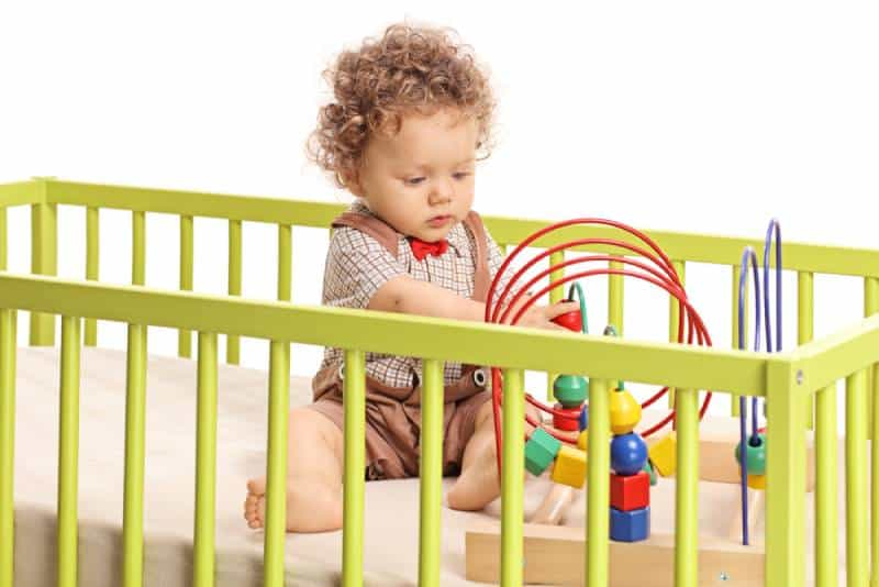 Baby boy playing with toys in a crib