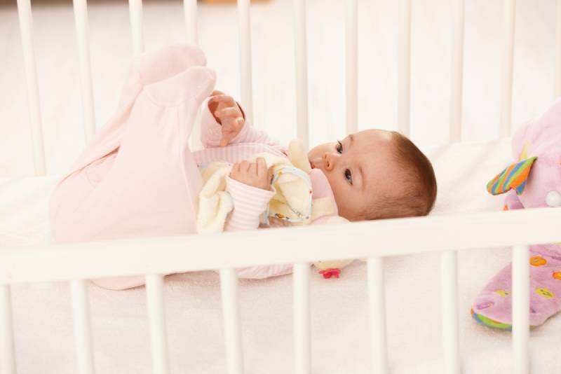 Cute baby playing with feet in baby crib, holding toy