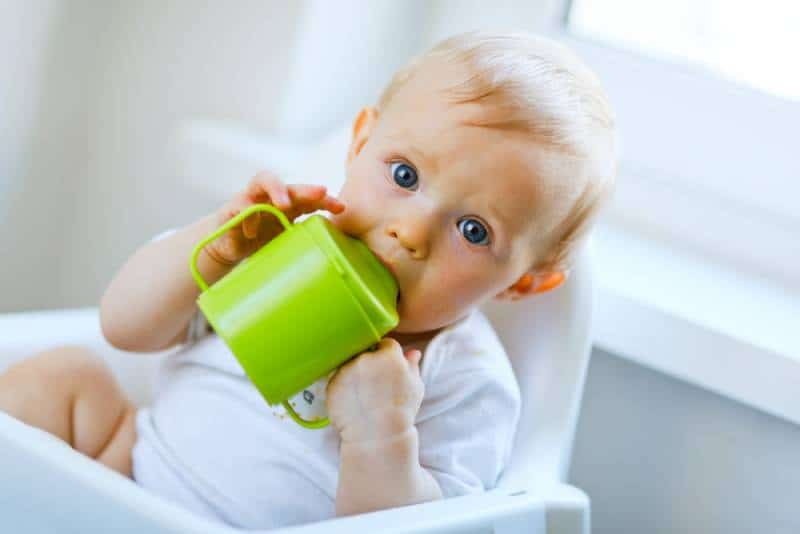 baby sitting in chair and drinking from baby cup