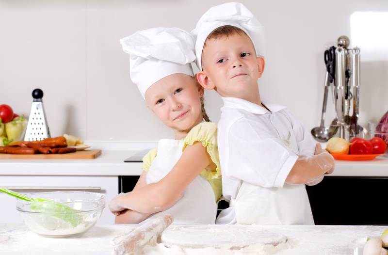boy and girl standing back to back in the kitchen