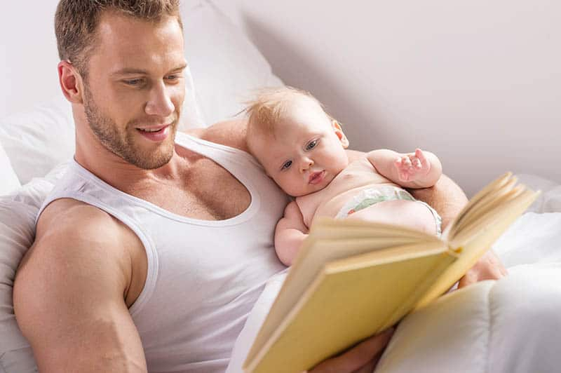 father reading a book with baby