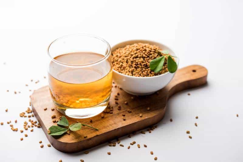 Fenugreek tea with seeds on wooden plate